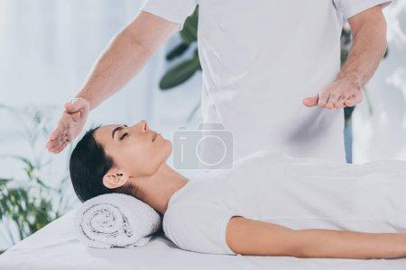 Photo pour Plan recadré de jeune femme calme recevant un traitement reiki de guérisseur masculin - image libre de droit