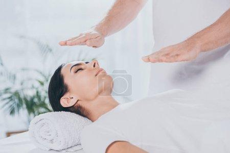 Photo pour Plan recadré de guérisseur masculin faisant séance de guérison reiki à la jeune femme avec les yeux fermés - image libre de droit