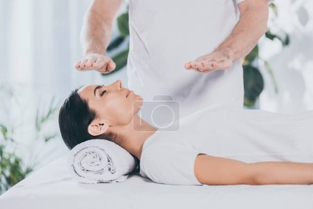 Photo for Cropped shot of male healer doing reiki treatment session to young woman with closed eyes - Royalty Free Image