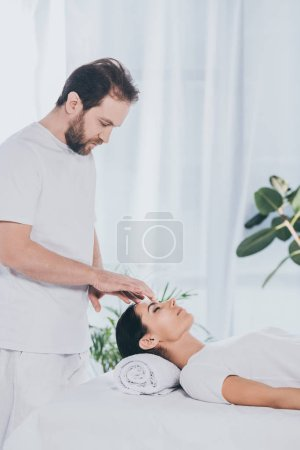 Photo for Side view of bearded healer doing reiki treatment session to young woman with closed eyes - Royalty Free Image