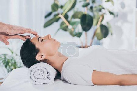 Photo pour Vue latérale de la jeune femme calme avec les yeux fermés recevant un traitement reiki sur la tête - image libre de droit