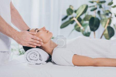 Photo pour Plan recadré de jeune femme calme avec les yeux fermés recevant une thérapie de guérison reiki - image libre de droit