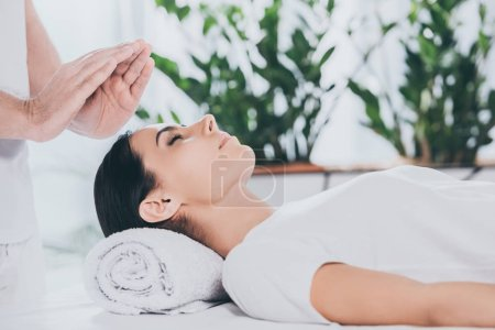 Photo for Cropped shot of calm young woman with closed eyes receiving reiki treatment - Royalty Free Image