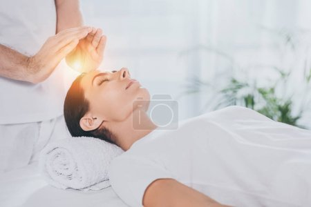 Photo for Cropped shot of young woman receiving reiki therapy above head - Royalty Free Image