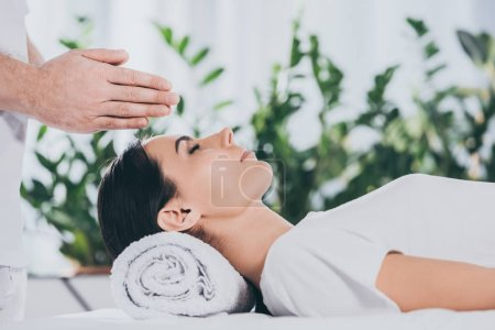 Photo for Cropped shot of young woman receiving reiki treatment above head - Royalty Free Image