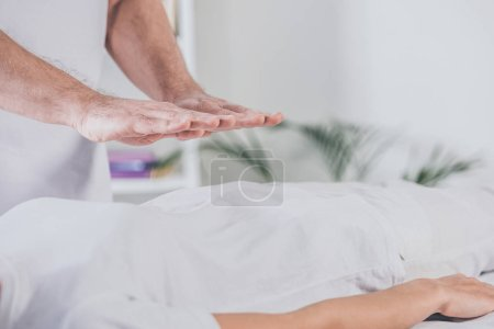 cropped shot of male therapist doing reiki healing session to woman