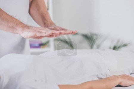 Photo pour Plan recadré de thérapeute masculin faisant séance de guérison reiki à la femme - image libre de droit