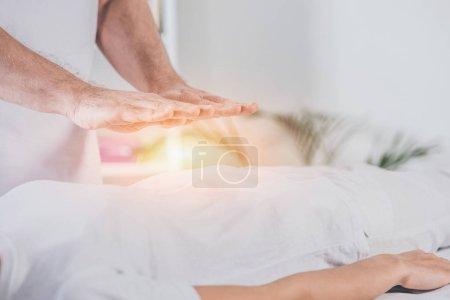 Photo pour Plan recadré de guérisseur masculin faisant séance de traitement reiki à la femme - image libre de droit