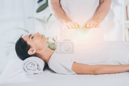 Photo for Cropped shot of young woman receiving reiki treatment above chest - Royalty Free Image