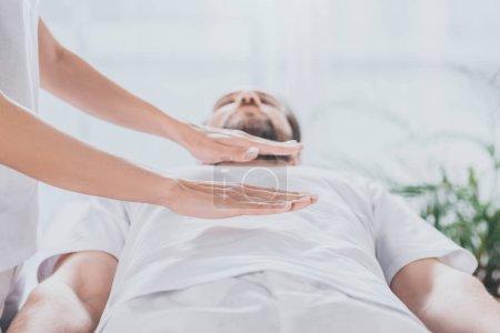 Photo pour Plan recadré de l'homme barbu recevant séance de guérison reiki au-dessus de l'estomac - image libre de droit