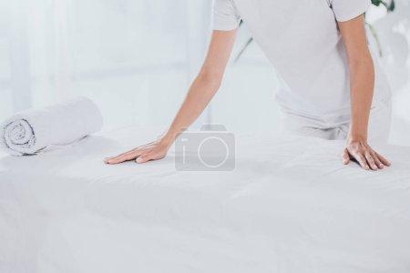 Photo pour Plan recadré de travailleur médical penché à la table de massage blanche avec serviette roulée - image libre de droit