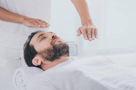 Photo pour Calme barbu homme couché sur la table de massage et les mains du guérisseur faire séance de traitement reiki - image libre de droit