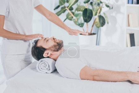 Photo pour Photo recadrée de guérisseur reiki fait séance de traitement pour calmer un homme barbu avec des yeux fermés - image libre de droit