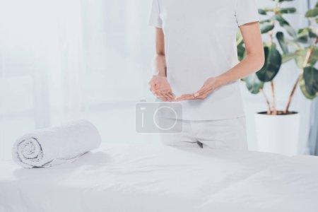 Photo pour Section médiane du guérisseur reiki debout près de la table de massage blanche - image libre de droit