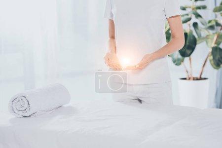 Photo pour Section médiane du guérisseur reiki avec de l'énergie lumineuse dans les mains debout près de la table de massage blanche - image libre de droit