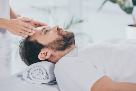 Photo for Calm bearded man receiving reiki treatment and looking up - Royalty Free Image