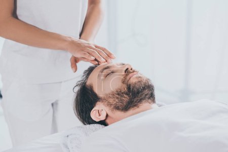 Photo for Calm bearded man with closed eyes receiving reiki healing therapy on head - Royalty Free Image
