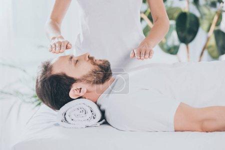 Photo pour Recadrée tir d'homme barbu calme les yeux fermés recevant reiki thérapie de guérison - image libre de droit