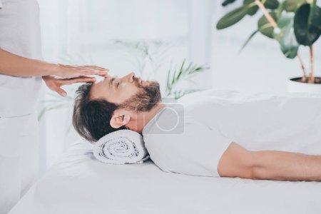 Photo pour Vue latérale de l'homme barbu calme avec les yeux fermés recevant thérapie de guérison reiki - image libre de droit