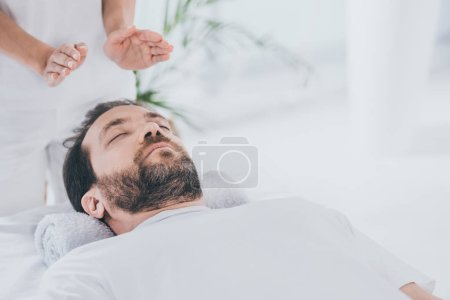 Photo for Calm bearded man with closed eyes receiving reiki healing session above head - Royalty Free Image