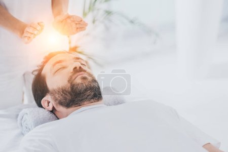 Photo for Calm bearded man with closed eyes receiving reiki healing session - Royalty Free Image