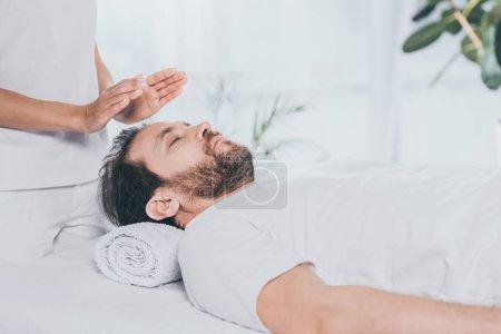 Photo pour Recadrée tir de calme barbu recevant reiki séance de guérison - image libre de droit