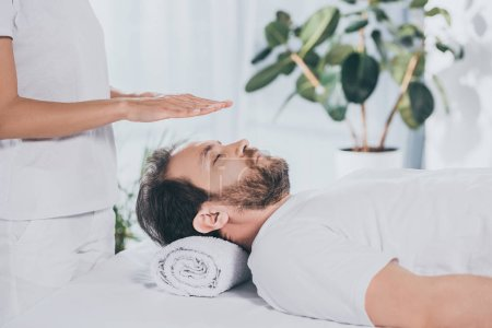 Photo pour Homme barbu calme les yeux fermés recevant un traitement reiki dessus de tête - image libre de droit