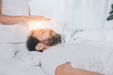 Photo pour Recadrée tir d'homme barbu calme les yeux fermés recevant un traitement reiki dessus de tête - image libre de droit