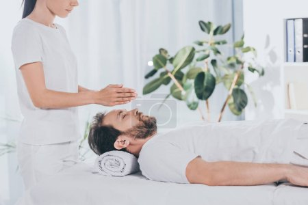 Photo for Side view of calm bearded man with closed eyes receiving reiki treatment on massage table - Royalty Free Image