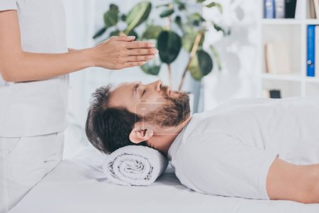 Photo for Side view of bearded man with closed eyes receiving reiki treatment above head - Royalty Free Image
