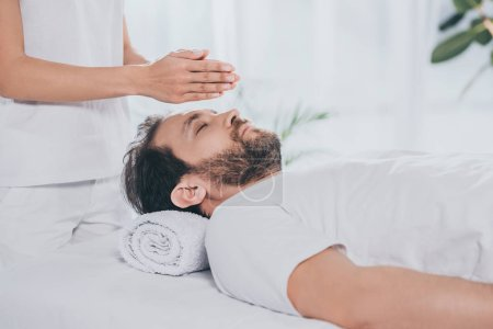 Photo for Cropped shot of bearded man with closed eyes receiving reiki treatment above head - Royalty Free Image