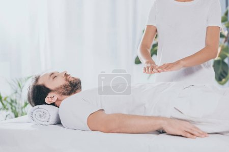 Photo for Cropped shot of calm bearded man with closed eyes lying on massage table and receiving reiki treatment - Royalty Free Image