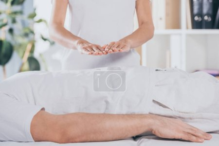 Photo for Cropped shot of man lying on massage table and receiving reiki treatment - Royalty Free Image