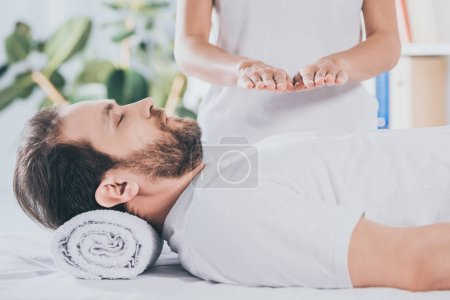 Photo for Cropped shot of calm bearded man with closed eyes receiving reiki treatment on chest - Royalty Free Image