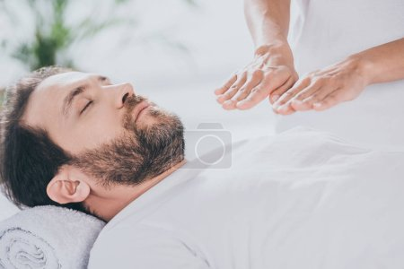 Photo for Cropped shot of calm bearded man with closed eyes receiving reiki treatment - Royalty Free Image