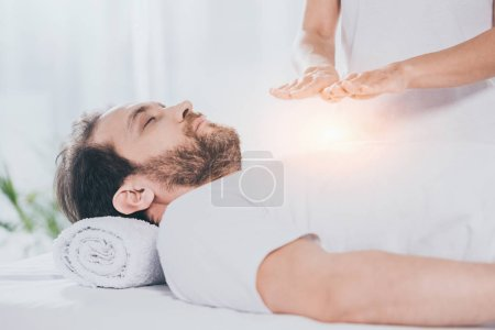 Photo for Cropped shot of bearded man with closed eyes receiving reiki treatment on chest - Royalty Free Image