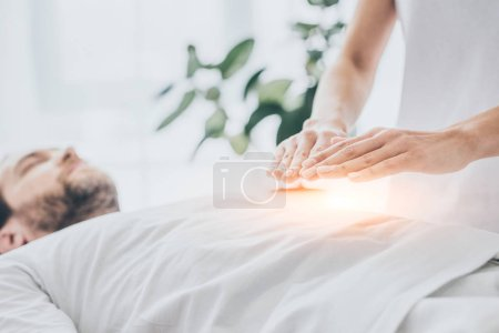 Photo for Cropped shot of man receiving reiki treatment on stomach - Royalty Free Image