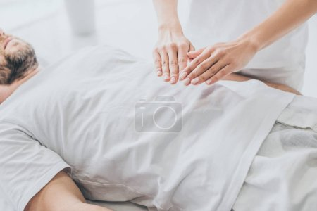 Photo for Cropped shot of bearded man receiving reiki treatment on stomach - Royalty Free Image