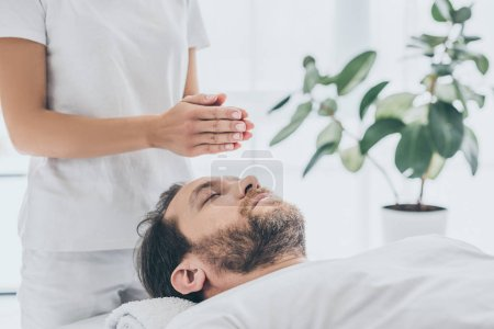 Photo for Cropped shot of female hands and bearded man receiving reiki treatment - Royalty Free Image