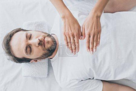 Photo pour Vue de dessus d'homme barbu, les yeux fermés recevant un traitement de reiki - image libre de droit