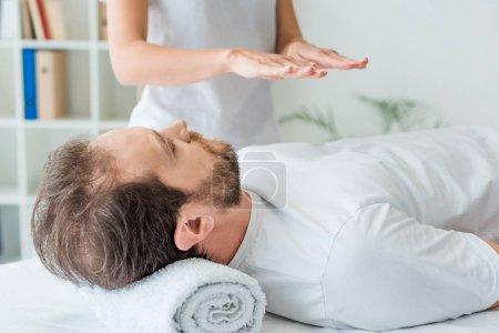 Photo pour Recadrée tir d'homme barbu allongé sur massage table et recevant un traitement de reiki - image libre de droit