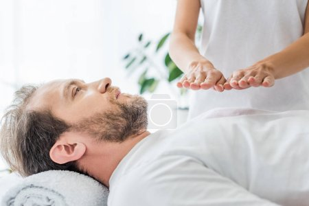 Photo for Cropped shot of bearded man receiving reiki treatment - Royalty Free Image