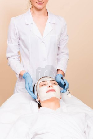 Photo for Beautician standing behind woman with cosmetic mask on face at beauty salon - Royalty Free Image