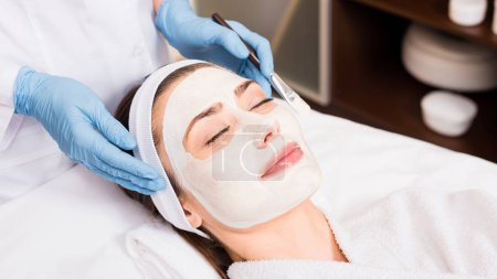 Photo pour Esthéticienne près de femme avec cosmétique masque sur le visage et la tenue de brosse cosmétiques au salon de beauté - image libre de droit