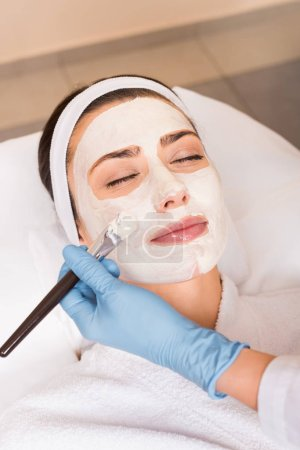 Photo for Beautician applying cosmetic mask to woman on face with cosmetic brush at beauty salon - Royalty Free Image