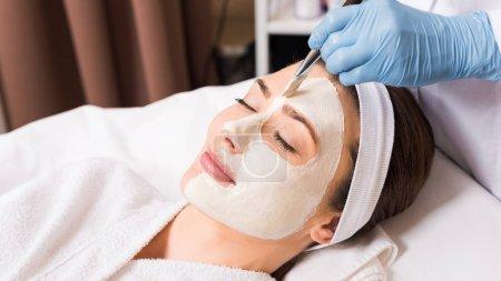 Photo pour Esthéticienne appliquant masque cosmétique à la femme sur demi-visage avec pinceau cosmétique au salon de beauté - image libre de droit