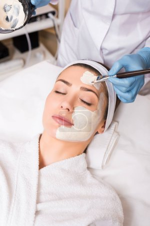 Photo pour Esthéticienne, appliquant des cosmétique masque sur le visage de femme avec brosse cosmétiques et tenant le bateau dans un salon de beauté - image libre de droit