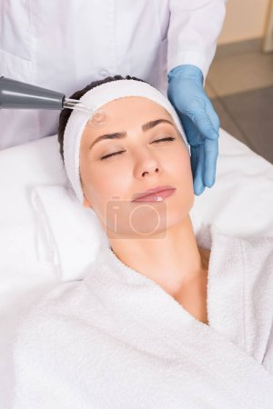 Photo for Beautician doing darsonvalization to woman on face at beauty salon - Royalty Free Image