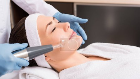 beautician making darsonvalization to woman at beauty salon