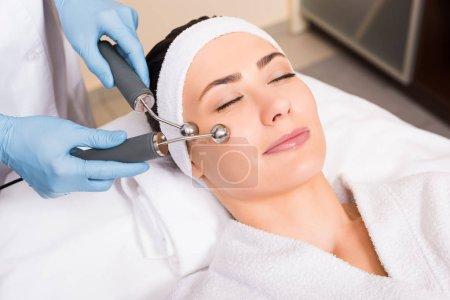 Photo pour Femme couché esthéticienne wile faire massage levant sur le visage avec l'équipement au salon de beauté - image libre de droit